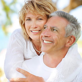 Mature couple smiling, thanks to dental implants