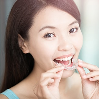 Female patient putting on Invisalign aligners