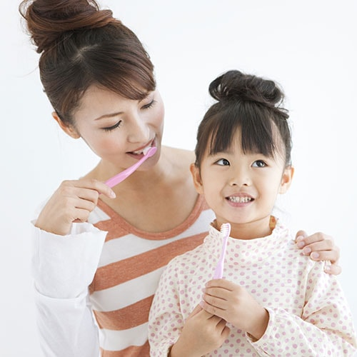 A mom showing her daughter how to brush her teeth.