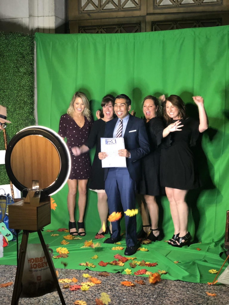Nashville Dentist Dr. Ashish Patel and his team posing for a photo in front of a green screen