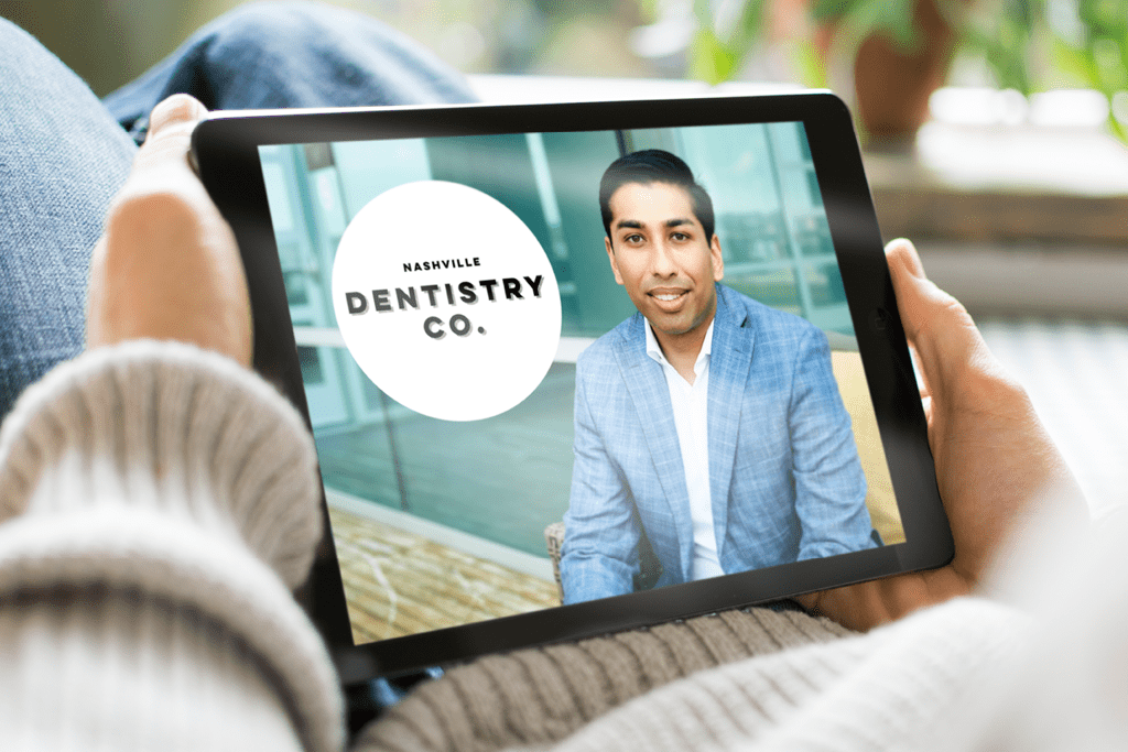 Someone holding an iPad, getting a virtual dental consultation from Dr. Ashish Patel