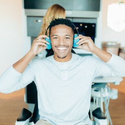A happy patient putting headphone on for KöR Whitening treatment